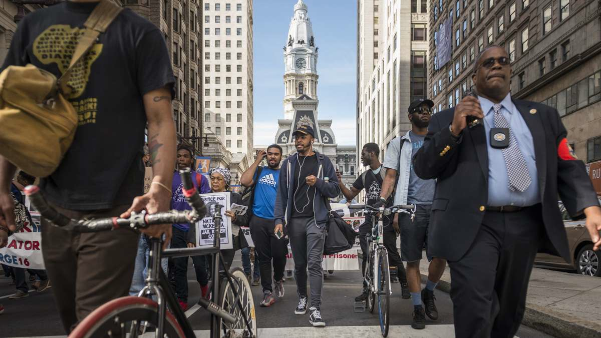 Police accompany protesters down South Broad Street near City Hall. (Branden Eastwood for NewsWorks