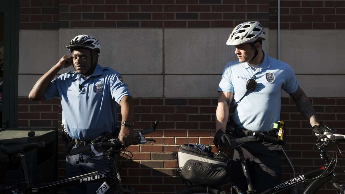 Two officers stand to the side as tensions rise outside of Whole Foods on South Street.
