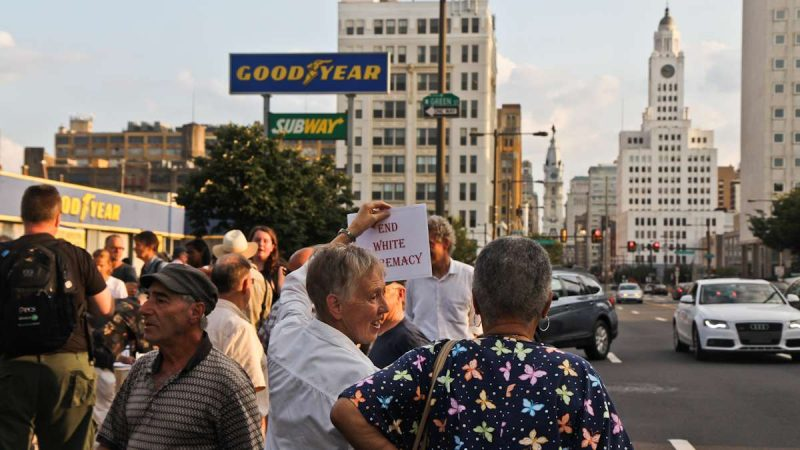 Marion Brown receives honks from motorists with her 'end white supremacy sign at the Philly is Charlottesville march Wednesday evening. (Kimberly Paynter/WHYY)