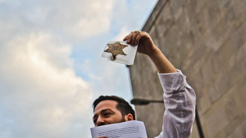 Rabbi Eli Freedman of Congregation Rodeph Shalom holds up a Star of David worn by a holocaust survivor at the Philly is Charlottesville march Wednesday evening. (Kimberly Paynter/WHYY)