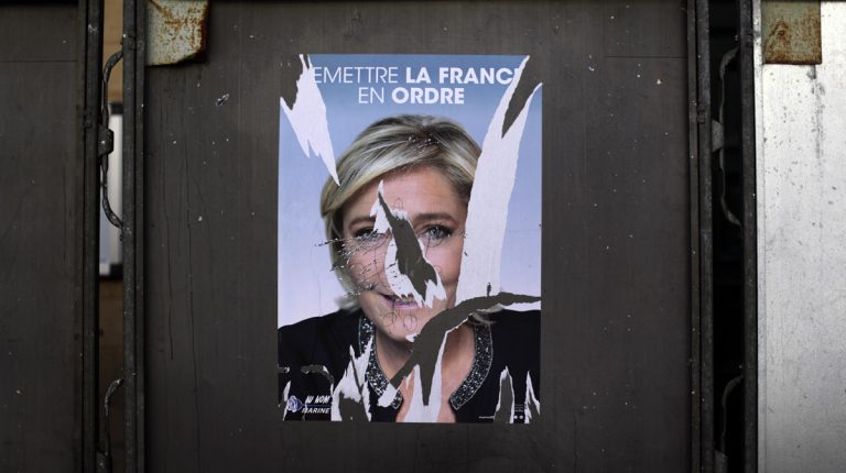 A torn poster showing a portrait of far-right leader and candidate for the 2017 French presidential election Marine Le Pen is seen outside at a polling station in Paris, Sunday, April 23, 2017. (AP Photo/Emilio Morenatti)