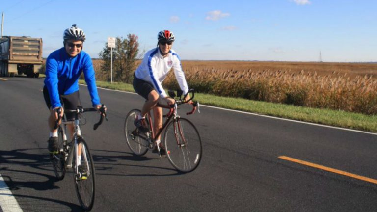 Then-Gov. Jack Markell (in blue) bikes along Rt. 9 near Port Penn in November with WHYY's Mark Eichmann.(File/WHYY)