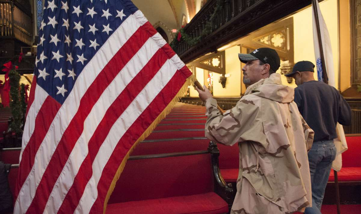 Benjamin Perez, a formerly homeless Army veteran unfurls the flag prior to the presentation of the colors at the Homeless Memorial Day service held at the Arch Street United Methodist Church in Center City. (Jonathan Wilson/for NewsWorks)