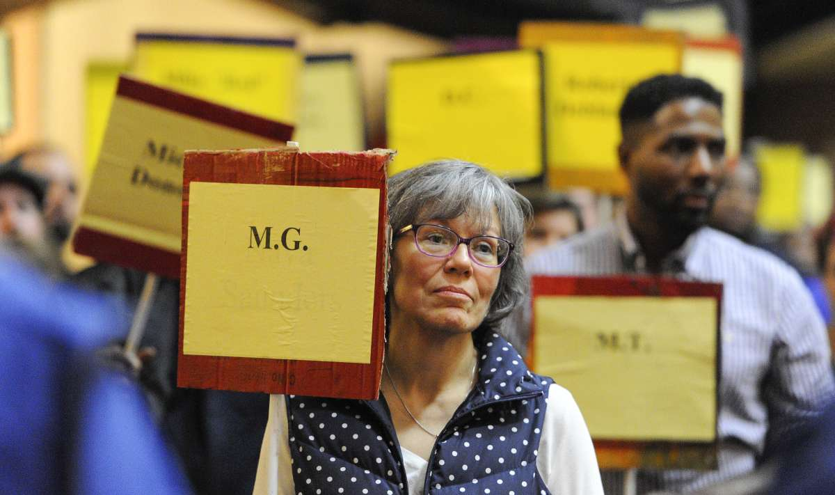 As the names of the deceased were read from the podium, participants rose from their seats holding the placards of homeless people who had passed away during the year. (Jonathan Wilson/for NewsWorks)