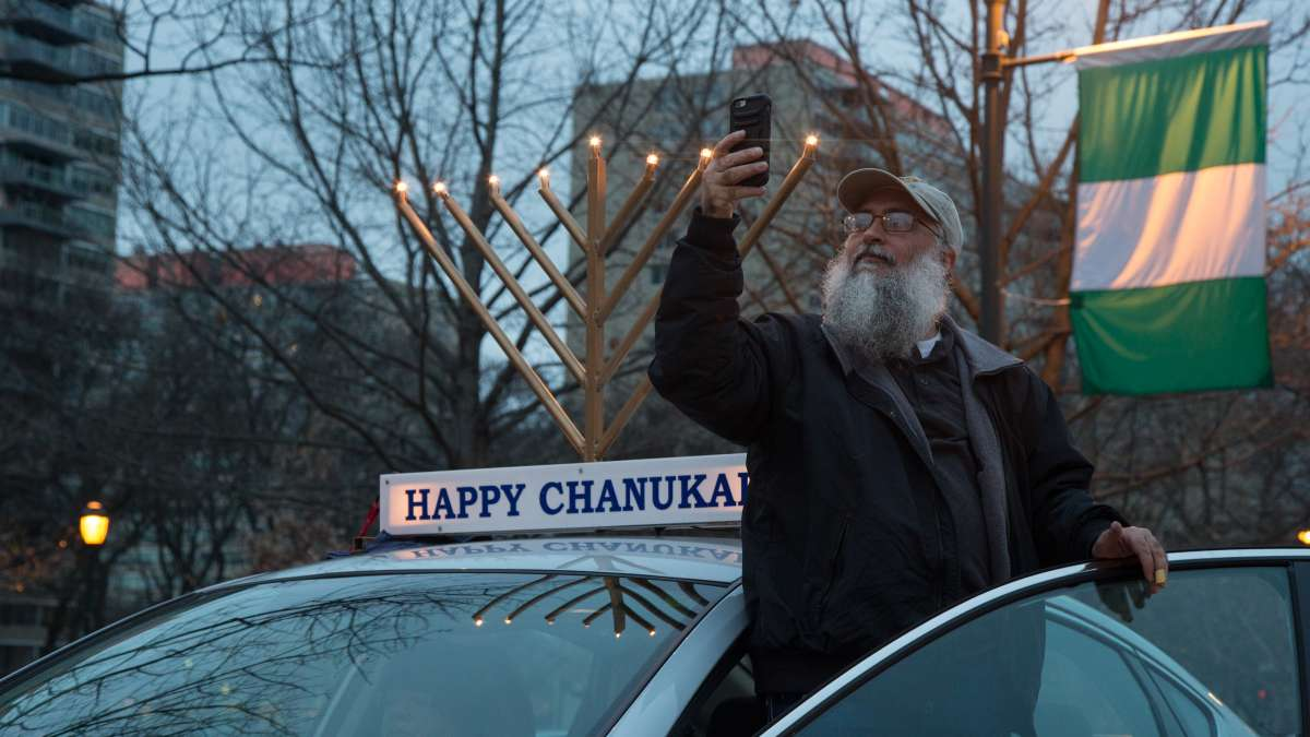 A driver captures the spectacle of 250 cars adorned with lit electric menorahs as they line up for the 10th Annual Car Menorah Parade put on by Rabbi Abraham Shemtov, the regional director of Chabad Lubavitch, an Orthodox Jewish movement.