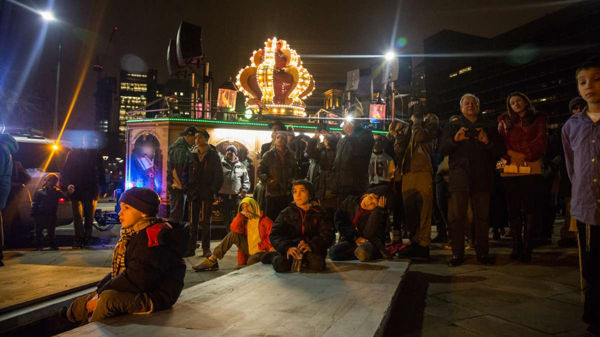 Children and adults gather under the massive menorah on Independence Mall as Rabbi Abraham Shemtov, the regional director of Chabad Lubavitch, says the blessings and lights the candles for the third night of Hanukkah December 26, 2016.