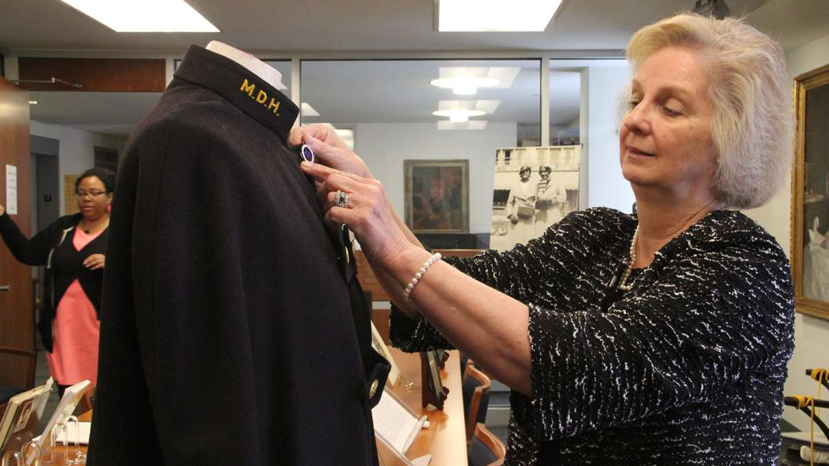 Dr. Jean Whelan, assistant director of the Barbara Bates Center for the Study of the History of Nursing, adjusts a pin on a Mercy Douglass nursing cape at the center's exhibit on the school, which trained black nurses for a segregated health care system. (Emma Lee/for NewsWorks)