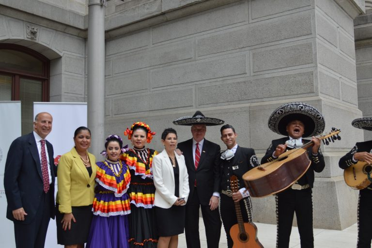 A sombrero-wearing Mayor Jim Kenney (third from right) and Alicia Kerber-Palma, Mexico's consulate general Alicia Kerber-Palma (fourth from right) take part in Mexican flag-raising ceremonies at Philadelphia City Hall. (Tom MacDonald/WHYY)
