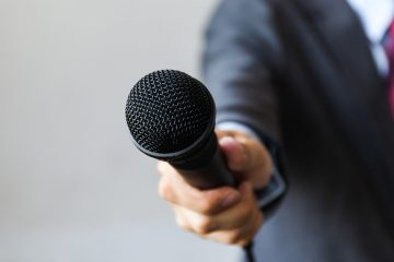 (<a href='https://www.bigstockphoto.com/image-124632608/stock-photo-man-in-business-suit-holding-a-microphone-conducting-a-business-interview%2C-journalist-reporting%2C-pub'>twinsterphoto</a>/Big Stock Photo)