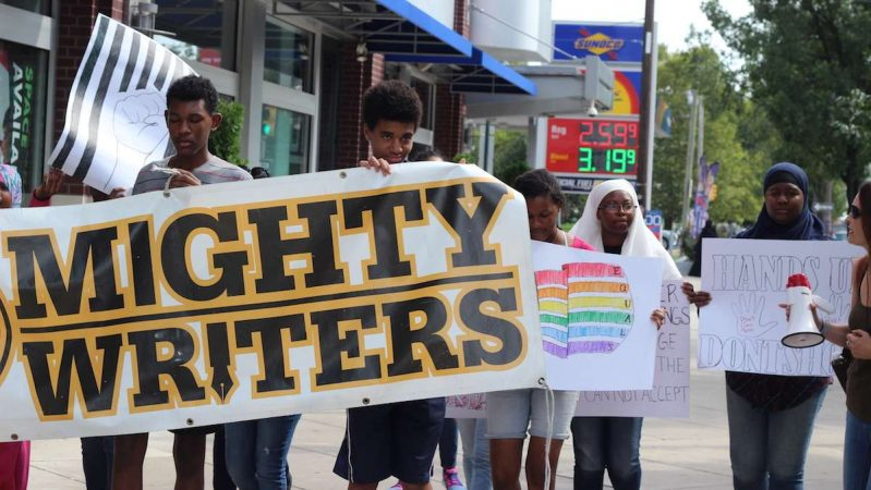 Ten students from Mighty Writers South marched down South Broad Street to City Hall with a banner and posters discussing LGBTQ issues, mass incarceration, police brutality and drug laws. (Emily Scott / WHYY)
