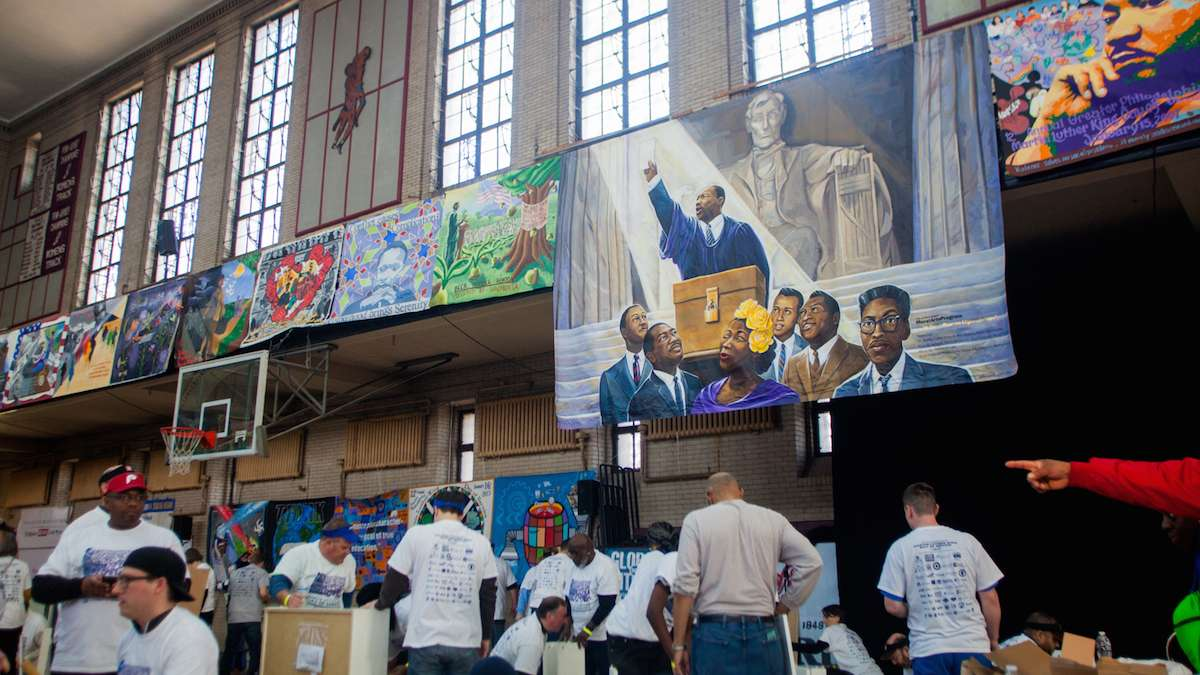 Underneath murals of Martin Luther King and other civil rights leaders volunteers worked on buidling bookshelves at Girard College on Martin Luther King Day. (Brad Larrison for NewsWorks)