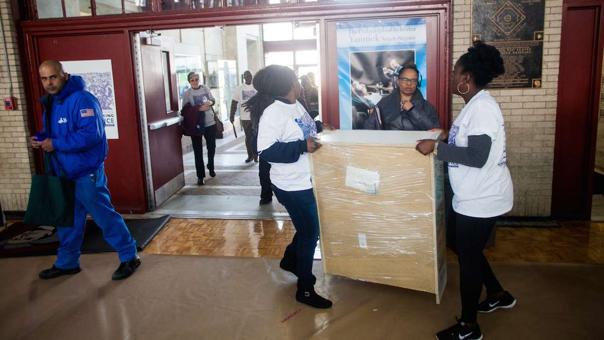 Volunteers with the literacy organization Read By 4th carried newly built bookshelves to be loaded on to trucks. (Brad Larrison for NewsWorks)