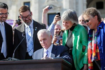 Minn. Governor Mark Dayton signs the state's same-sex marriage bill into law in front of the Capitol in Saint Paul on Tuesday as bill authors Sen. Scott Dibble, second from left, with his partner Richard Leyva, and Rep. Karen Clark, second from right, and her partner Jacqueline Zitaduring, look on. (Craig Lassig/AP Images for Human Rights Campaign)