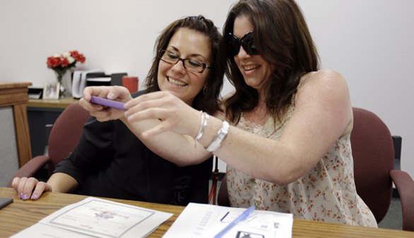 Tamara Davis, (left), and Nicola Cucinotta snap a photograph of their marriage license they obtained at a Montgomery County office despite a state law banning such unions, Wednesday, July 24, 2013, in Norristown, Pa. Five same-sex couples have obtained marriage licenses in the suburban Philadelphia county that is defying a state ban on such unions. (Matt Rourke, AP Photo)