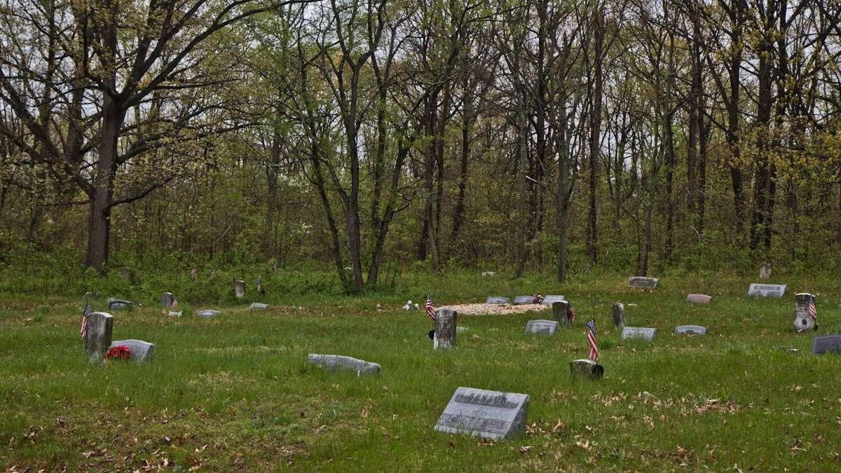 The graves of Mount Peace Cemetery stretch back into the woods.