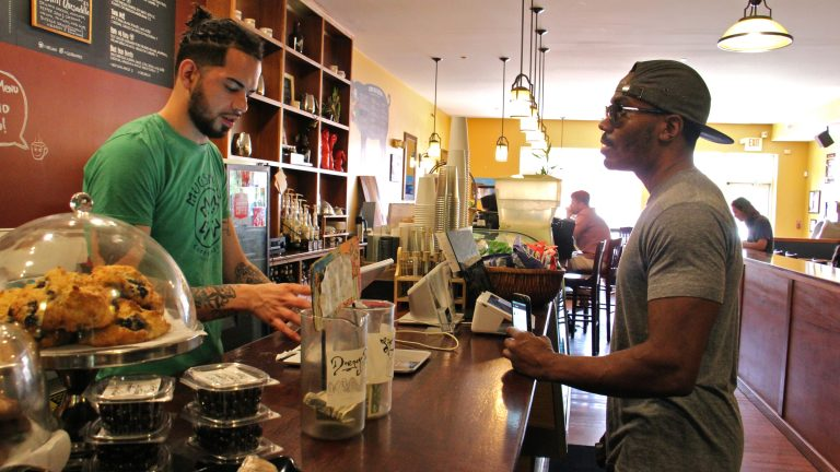 José Laboy (left) takes a customer's order at Mugshots café on Fairmount Avenue. (Emma Lee/WHYY)