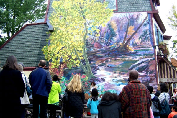 <p><p>Residents gathered outside of Bredenbeck's Bakery in Chestnut Hill on Saturday to admire the neighborhood's first mural. (Bob O'Brien/for NewsWorks)</p></p>