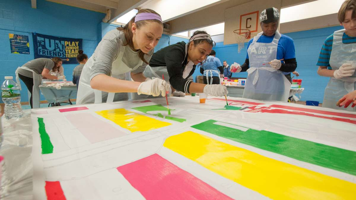 Amanda DeSenna (left) and Marielle Fortune paint one of the canvas squares that will make up Shira Walinsky's new mural, ''Migrating Home.''