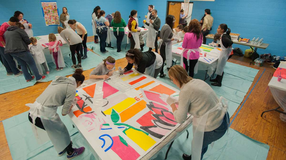 Nearly 50 volunteers participate in the mural painting at the Capitolo Playground Center.