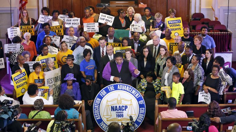 North Carolina NAACP president, Rev. William Barber, center at podium gestures as he is surrounded by supporters during a news conference at the Third Street Bethel AME Church in Richmond, Va., Tuesday, June 21, 2016. (AP Photo/Steve Helber)