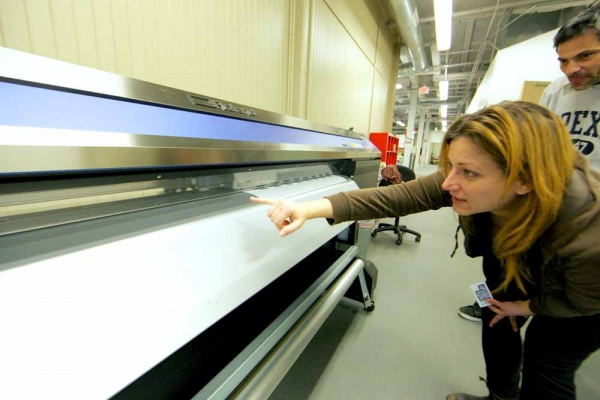 "<p><p>The Roland XR-640 Vinyl Print/Cut System 64"" is printing vinyl stickers for the upcoming event. Rachel Kotkoskie, facility coordinator at NextFab and photographer, is pointing out the blade on the printer head as it prints. (Nat Hamilton/for NewsWorks)</p></p>"