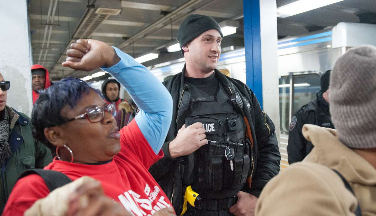 An amused SEPTA Police Officer watches the No Pants participants on the Market-Frankford Line platform.