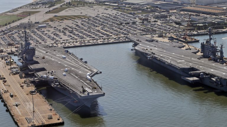 Nuclear-powered aircraft carrier USS Dwight D. Eisenhower, left, and USS George Washington, right, sit pierside at Naval Station Norfolk in Norfolk, Va., Wednesday, April 27, 2016. There is growing consensus among Washington Republicans that climate change is a threat to U.S. security. Norfolk, Virginia, headquarters of the Atlantic fleet, now floods several times a year. (AP Photo/Steve Helber, file)