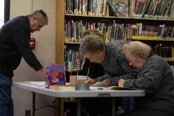 <p><p>Poll workers fill out the necessary paperwork at the Roxborough Library. (Francis Hilario/for NewsWorks)</p></p>