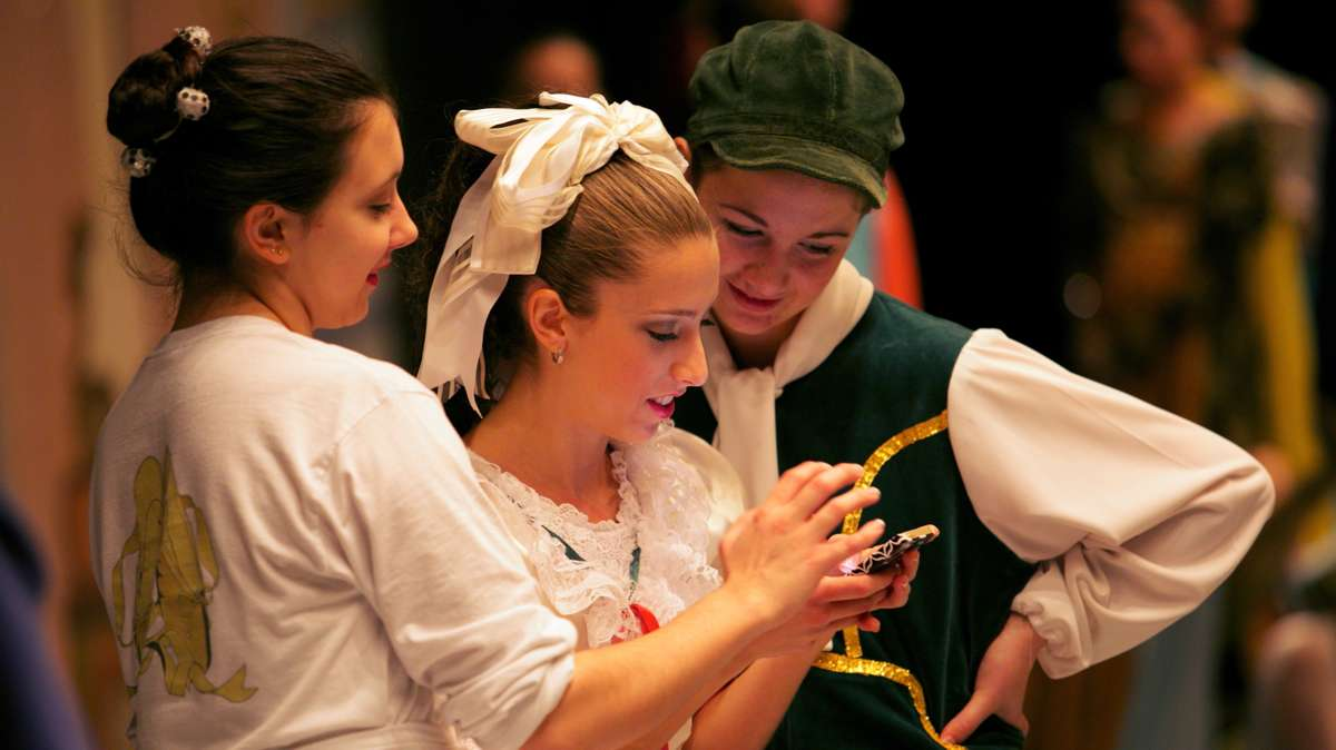 Ballerinas unwind before the performance, sharing things on their phones. (Nathaniel Hamilton/for Newsworks)