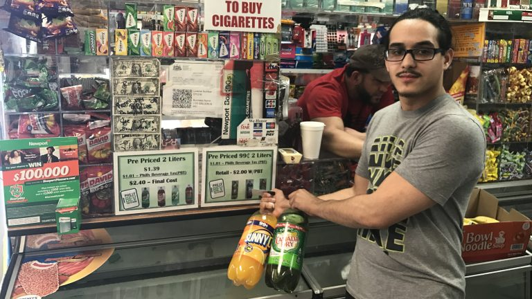 Frayby Perelta holds up 2-liter bottles of soda that are now mislabeled with the wrong price because of Philadelphia soda tax. A sign in the bodega he operates explains that the tax has doubled the price. (Bobby Allyn/WHYY)