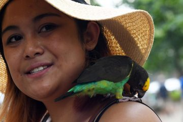 Kristin Buenaventura, of West Philadelphia, smiles as her pet-bird Pepino sits on her shoulder at the annual Clark Park Festival in West Philadelphia, On Saturday July 7th, 2017. (Bastiaan Slabbers for NewsWorks)