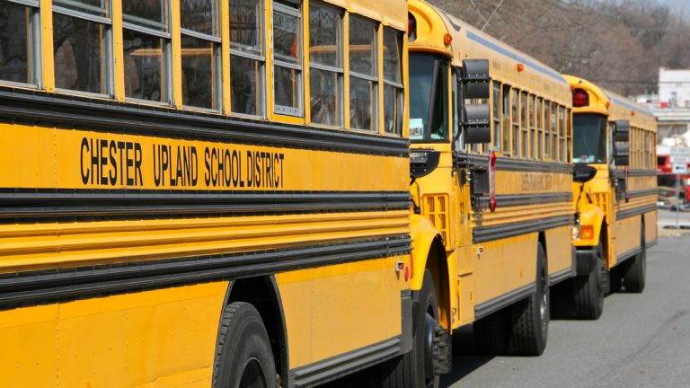 Buses from Chester Upland School District await dismissal from Chester High School on West Ninth Street. (Emma Lee/WHYY)