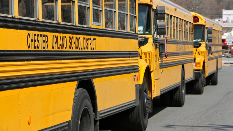 Buses from the financially troubled Chester Upland School District await dismissal from Chester High School on West Ninth Street. (Emma Lee/for NewsWorks)