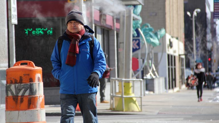 Bundled up against the extreme cold, a man crosses the street at Eighth  and Arch in Philadelphia (Emma Lee/WHYY)