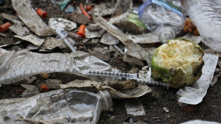 Thousands of used needles litter the ground at a heroin encampment in Kensington. (Emma Lee/WHYY)