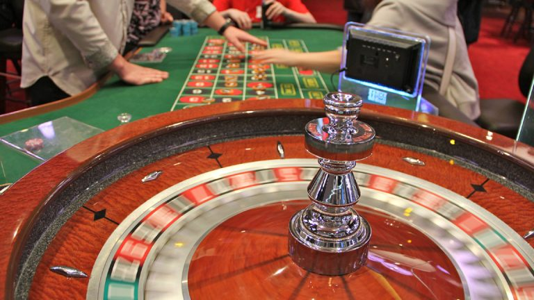 Patrons lay their bets as the wheel turns at SugarHouse Casino in Philadelphia. (Emma Lee/WHYY, file)