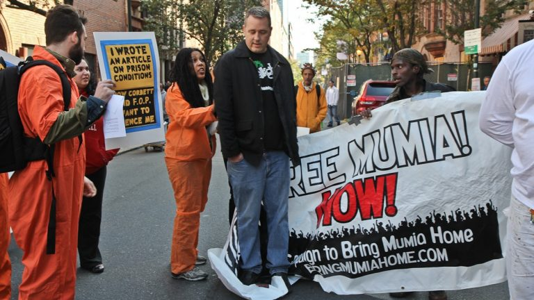 Mumia supporters clash with event attendees at a bill signing on the street where Daniel Faulkner was killed. (KImberly Paynter/WHYY)