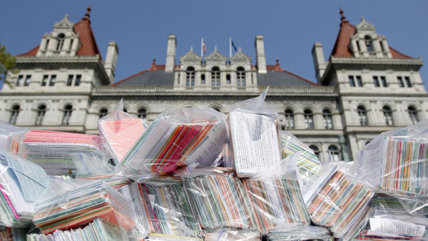 This May 21, 2013, image shows some of the 400,000 signed postcards to be delivered to N.Y. Assembly members, calling on them to repeal the NY SAFE Act, stacked on a table outside the Capitol during a Second Amendment rally. (AP Photo/Mike Groll, file)