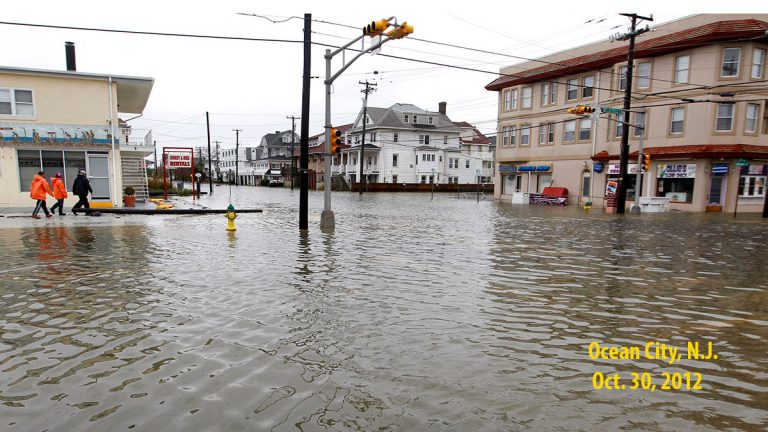 FILE - In this Oct. 30, 2012 file photo, people walk along a flooded intersection of 8th Street and Atlantic Avenue, in Ocean City, N.J., after the storm surge from Superstorm Sandy flooded much of the town. (AP Photo/Mel Evans, File)