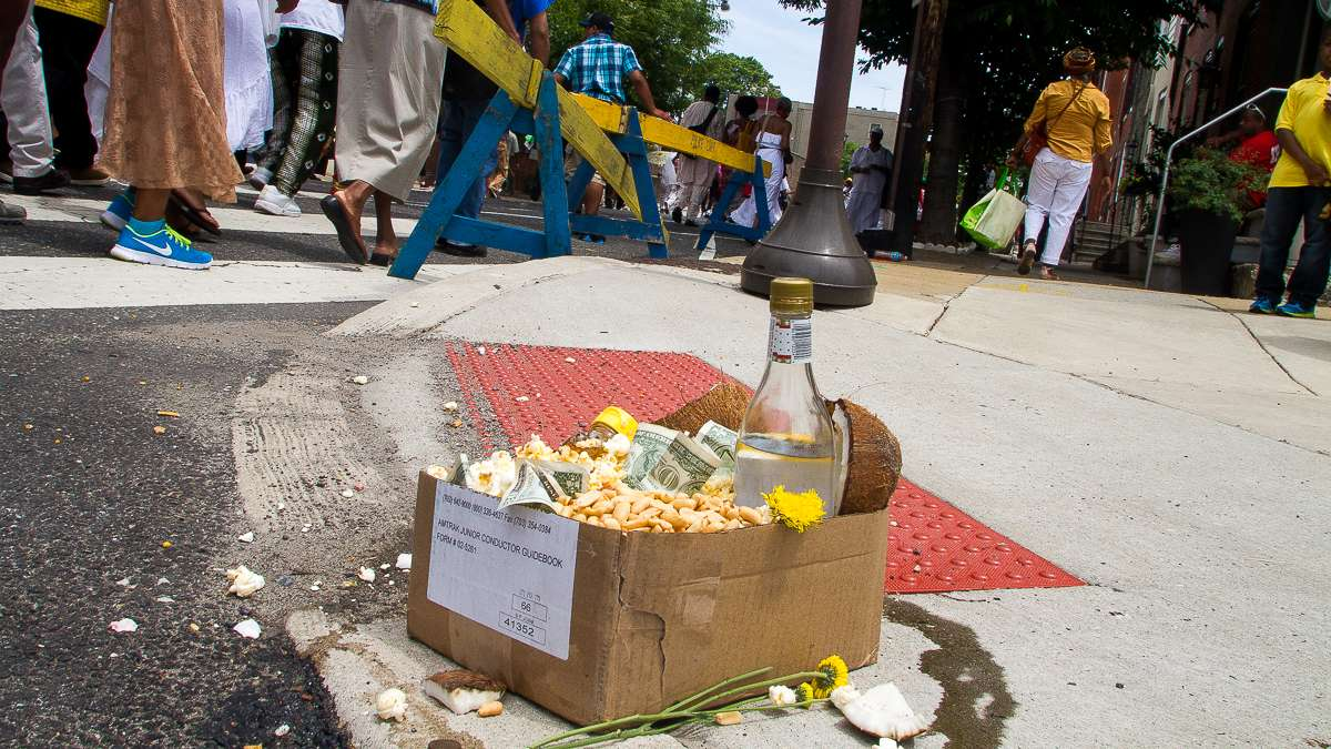 Offerings of popcorn, peanuts, honey and other foods accumulate on the corner of 27th and South streets during the Odunde Festival. (Brad Larrison/for NewsWorks)