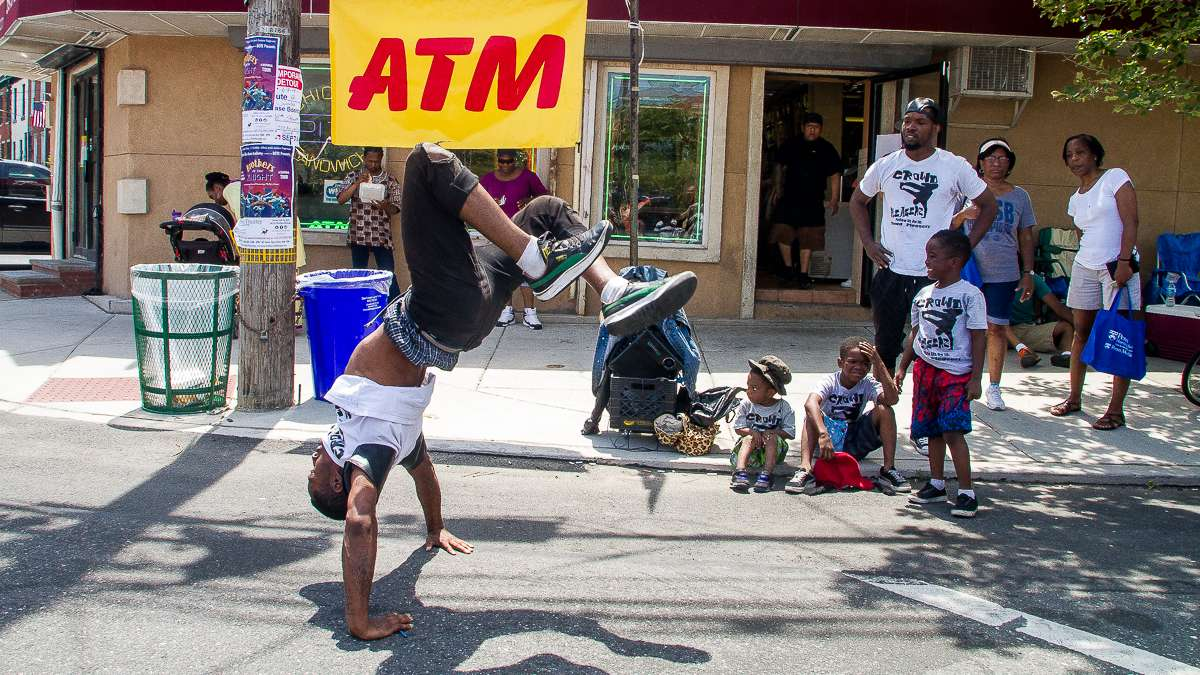 Dante Thompson of the Crowd Pleaserz group break dances at the corner of Bainbridge and Grays Ferry Avenue during the Odunde Festival. The festival blends African cultural heritage with modern African American culture. (Brad Larrison/for NewsWorks)
