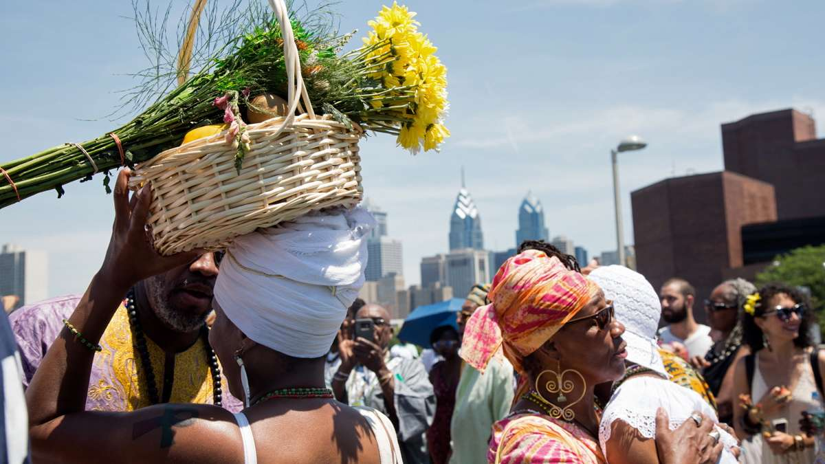 A woman carries offerings for the river goddess Oshun at the begining of the Philadelphia Odunde Festival.