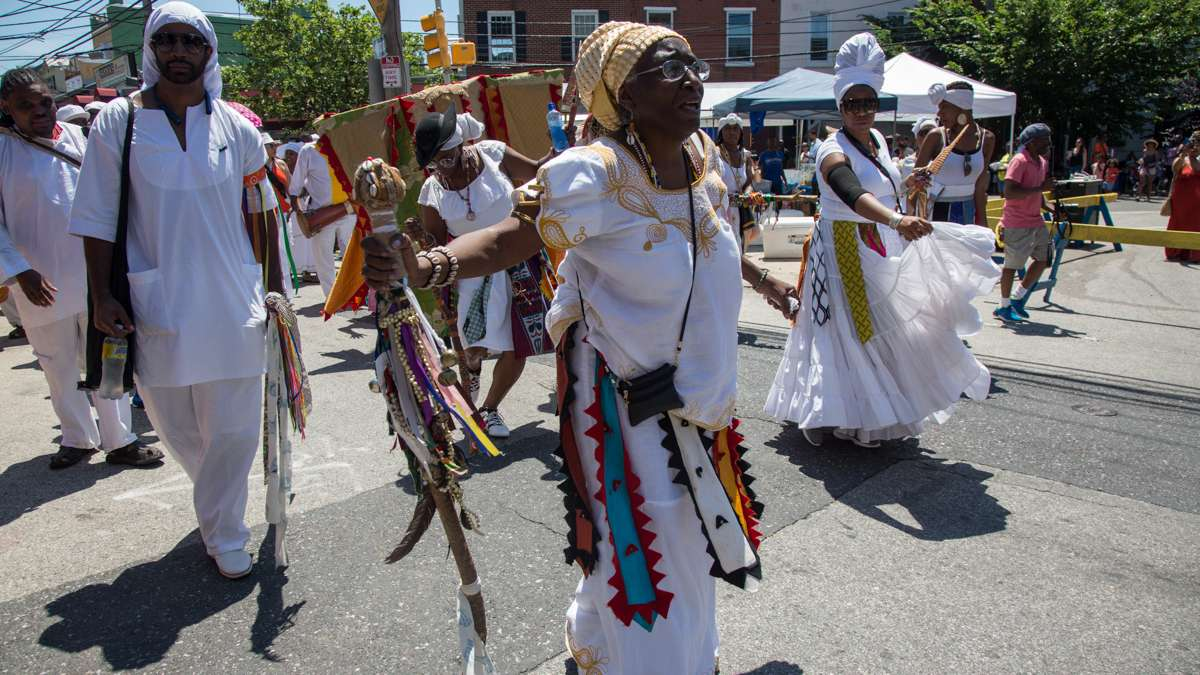 E Iya Olakunle Olundia (center) leads the procession toward the Schuylkill River to bring offerings to the Yoruba river goddess at the opening of the Philadelphia Odunde Festival. Dancers in white surround the two costumed dancers to protect the spirits of their ancestors.