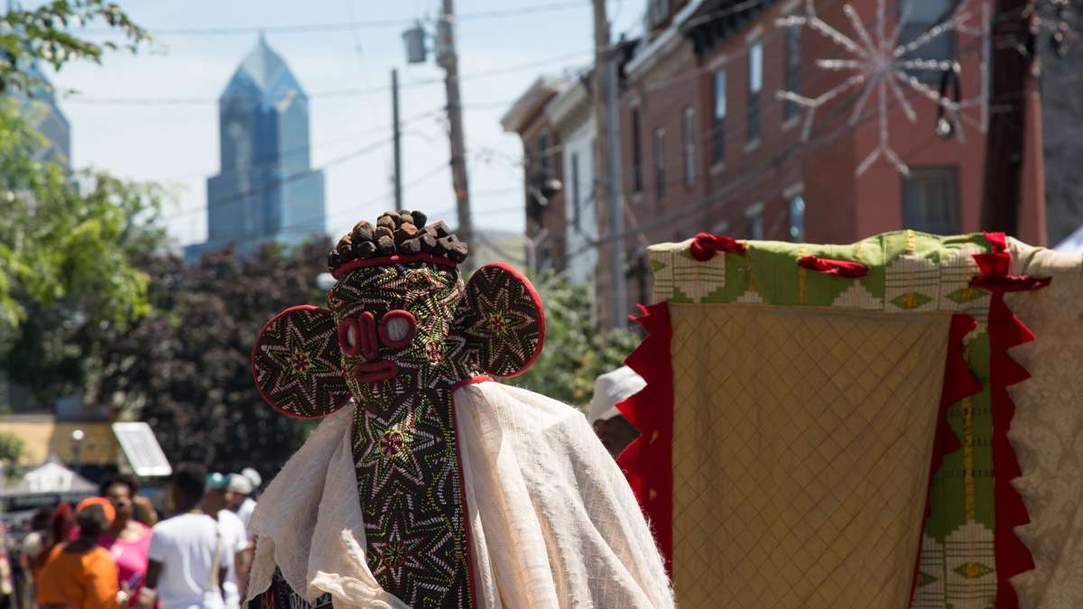 A physical representation of Egungun, or ancestors, dances in the procession toward the Schuylkill River to bring offerings to the Nigerian river goddess at the begining of the Philadelphia Odunde Festival.
