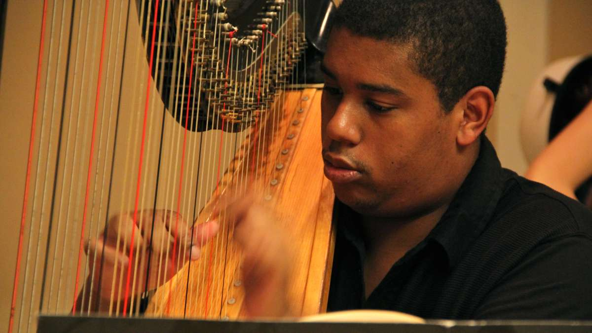 CAPA graduate Jordan Thomas plays the harp with the All City Orchestra, which is preparing for a trip to Italy. (Emma Lee/WHYY)