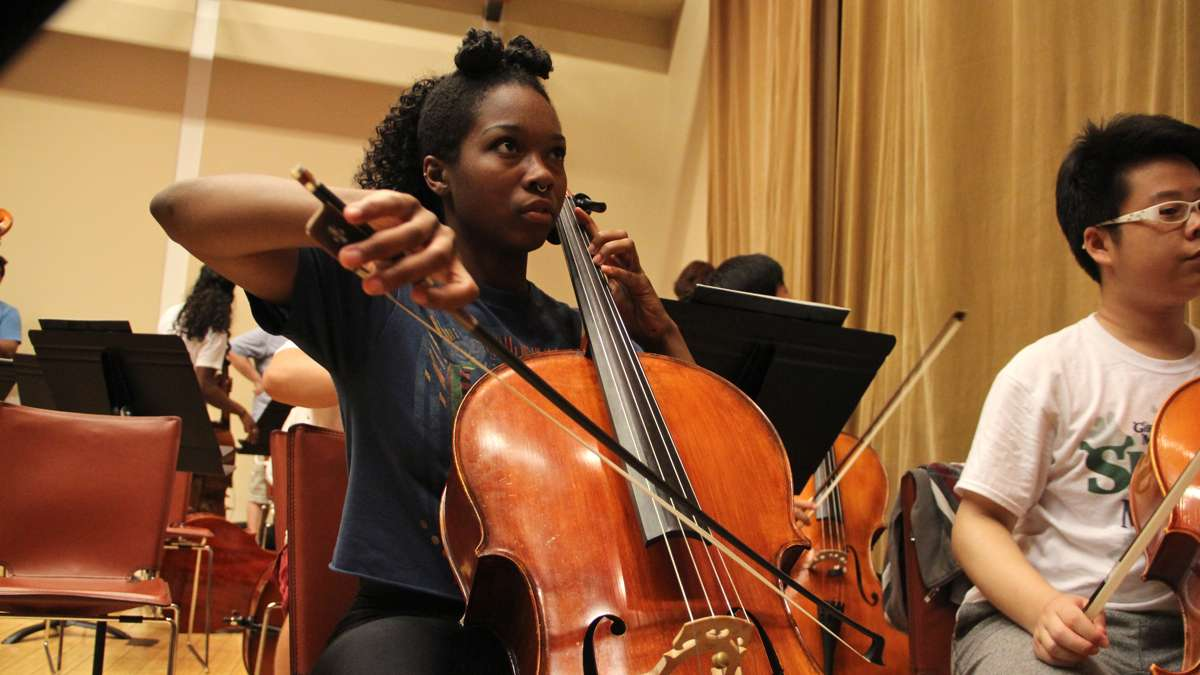 Tayana Woodton, a graduate of Girard Academy of Music, warms up before rehearsal with the All City Orchestra. (Emma Lee/WHYY)