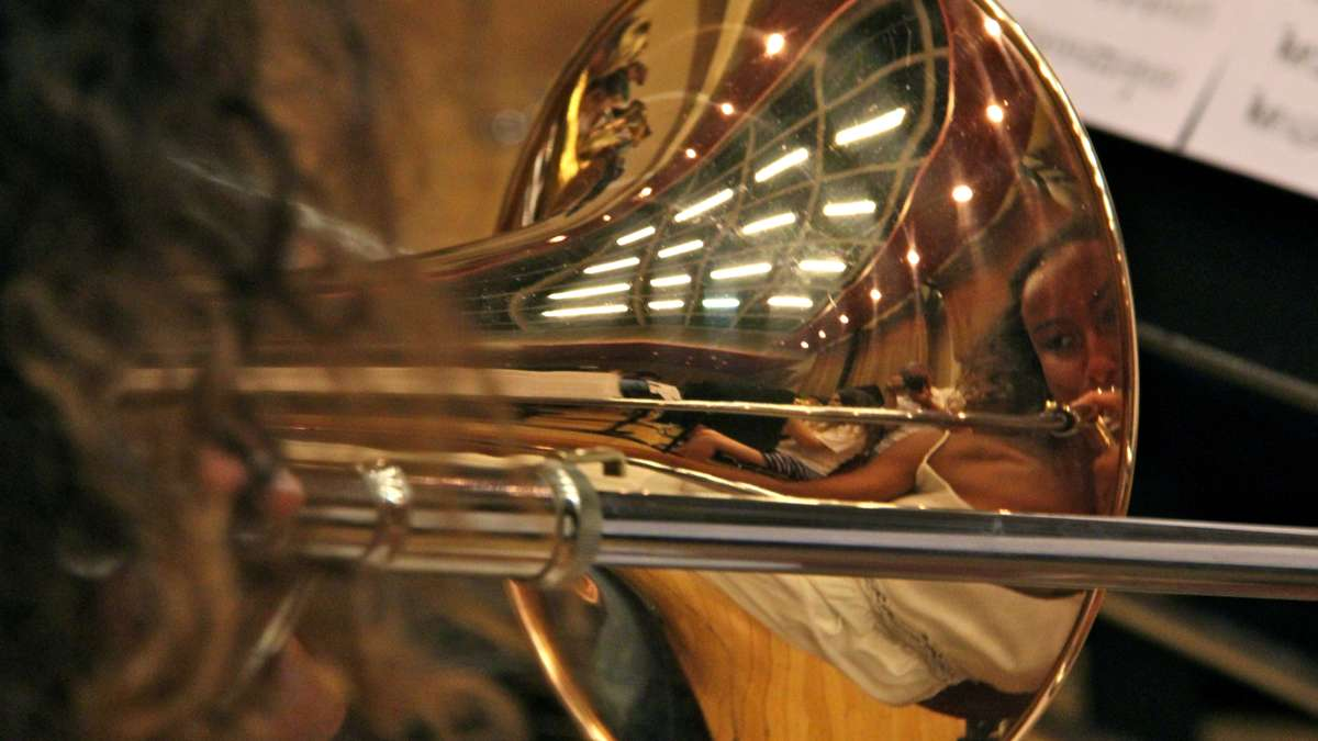 Masterman High School's Ariannis Hines is reflected in the bell of her trombone as she rehearses with the All City Orchestra.(Emma Lee/WHYY)