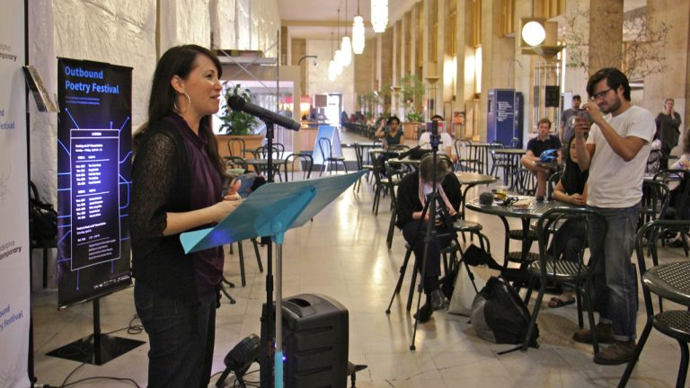 Michelle Myers speaks her poetry at the Outbound Poetry Festival at 30th Street Station. (Emma Lee/WHYY)