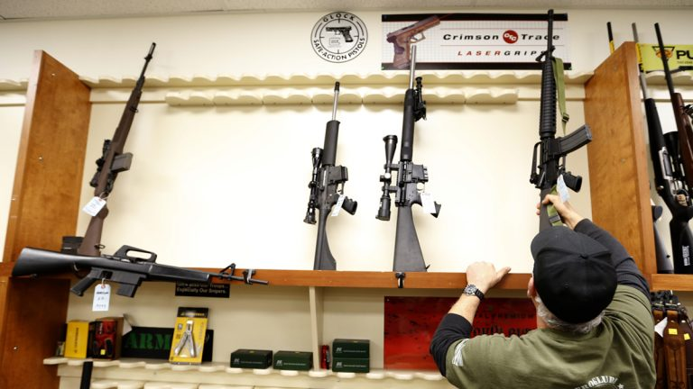 In this file photo, a store manager replaces one of the five used military style rifles onto a rack that usually has more than 20 models for sale in in New Castle, Pa.  (AP Photo/Keith Srakocic)