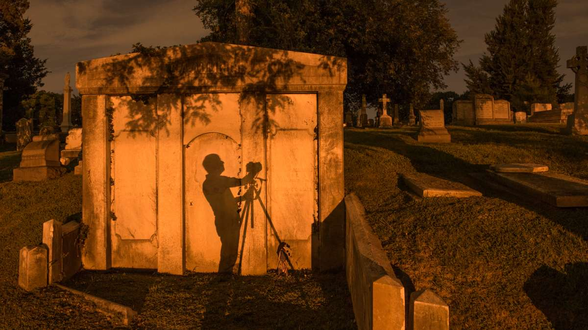 A photographer's shadow is cast against the wall of a mausoleum from the illumination of street lights.